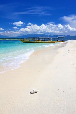 yellow boats: Beach on Gili Trawangan island, Indonesia, with yellow boats, white sand and small rock in foreground on sunny day