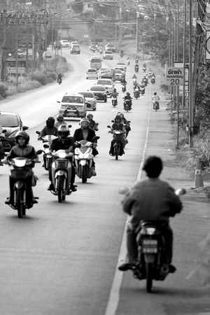 outbound: Busy traffic on street in Phuket, Thailand, with a motorcycle going opposite way in black and white