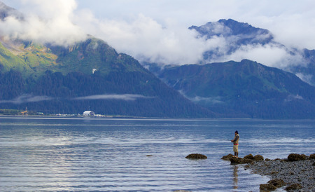 Seward, Alaska, United States - September 10, 2014: Man in his 50s standing alone on rock on beach in Resurrection Bay, Seward, Alaska and fishing for salmon. Mountains on opposite side of the bay are partly covered in clouds.