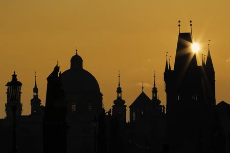 dazzle: Golden silhouette of the Prague Charles Bridge and towers and churches with dazzle sun ray over the bridge tower. Magical picture of the Czech capital city, Old Town, Prague.