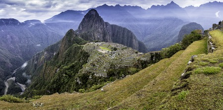 salkantay: Panoramic shot of the lost Inca city of Machu Picchu with yellow grassland, clouds and Huayna Picchu in the background.