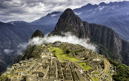 salkantay: Ruins of Machu Picchu and Huayna Picchu covered by mystical cloud. Panoramic summer view from above. Stock Photo