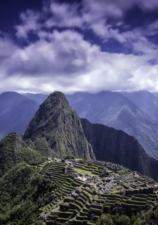 salkantay: Vertical picture of the lost Inca city of Machu Picchu. Machu Picchu archaelogical ruins in the clouds on the blue sky. Photo from above. Stock Photo