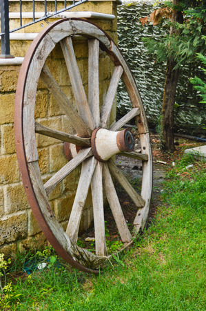 the coachman: a carriage wheel leaning against the wall