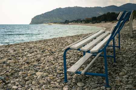 lonelyness: a bench on a stony beach Stock Photo
