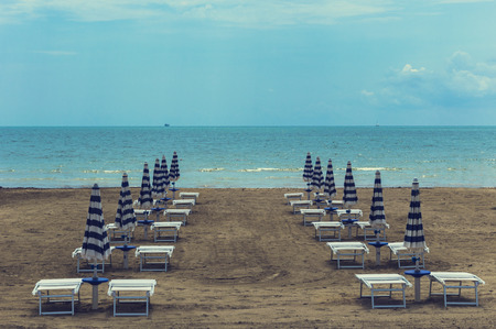 seaa: deserted beach with umbrellas in a row Stock Photo