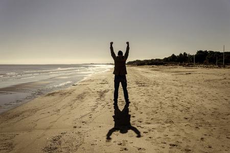 personas caminando: sombra en la playa