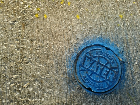 Water drain lid with blue paint on concrete surfaces Tampa Florida