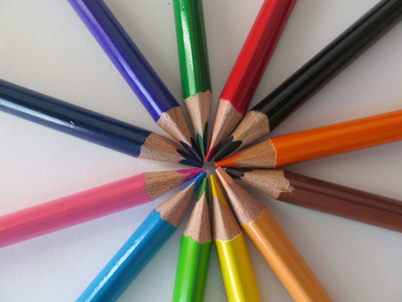 inwards: Group of coloured wooden pencils pointing inwards Stock Photo