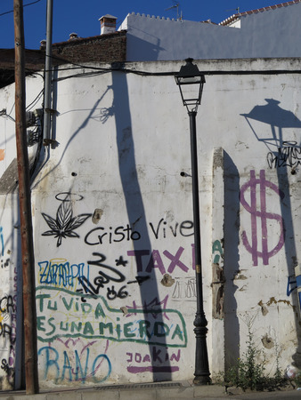 defaced: Sun and shadows on Wall covered in writing in Alora Andalucia Stock Photo
