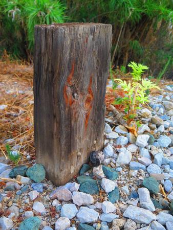 ballast: Short weathered Wooden Post in Railway Ballast Stock Photo