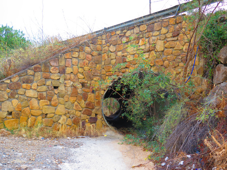eau de pluie: Flowers and shrubs growing at entrance to rainwater culvert in Alora countryside Andalucia Banque d'images