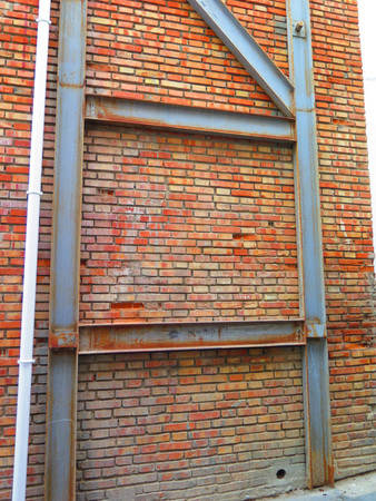 girders: Brick wall braced and supported by iron girders in Alora, Andalucia