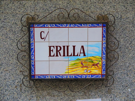 describing: Decorative Alora street sign, tiled and surounded by wrought iron border