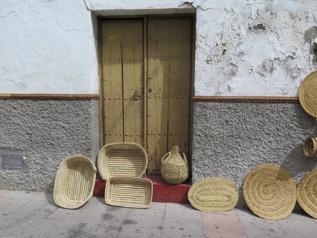 backstreet: Old wooden door and Baskets and mats in Alora backstreet, Andalucia Stock Photo