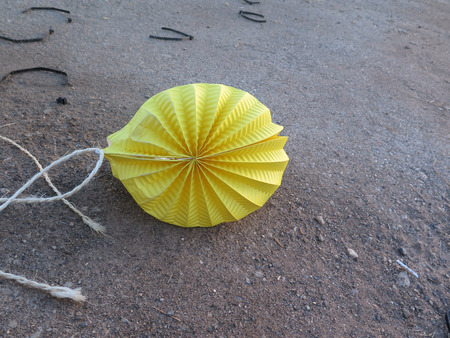 discarded: Discarded yellow paper lantern on roadside in Alora countryside