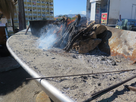 lunchtime: Logs smouldering on seaside barbeque ready for lunchtime trade