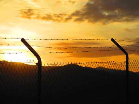 barbed wire fences: Barbed wire fence against Sunrise in Alora countryside, Andalucia