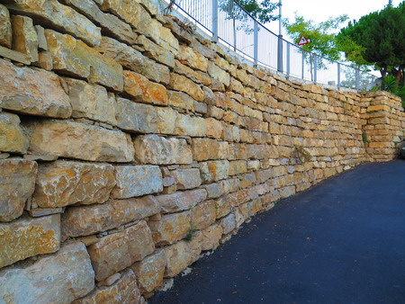 residential street: Retaining wall from granite blocks in residential street in Alora, Andalucia Stock Photo