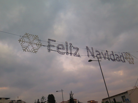 suspended: Suspended christmas greeting over road in Alora, Andalucia Stock Photo