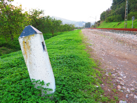 distance marker: White concrete railway distance marker in weed covered countryside near Alora, Andalucia
