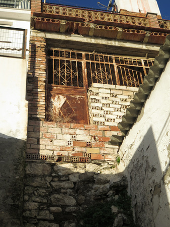 andalucia: Rusty metal back door leading to a dangerous drop in Alora street, Andalucia