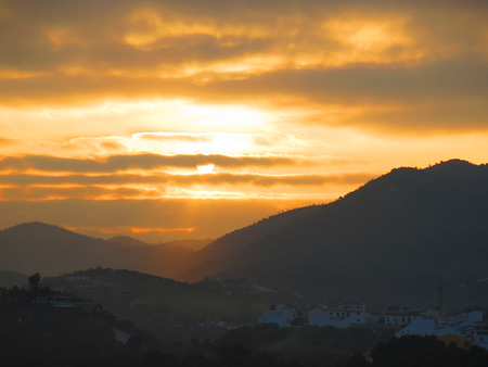 clowds: silhouette at orange dawn clowds in village of Alora, Andalucia Stock Photo