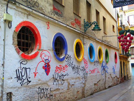 defaced: Defaced wall and Colourful Portholes in Malaga Street Stock Photo