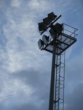 halogen lighting: black silhouette of spotlight tower against cloudy sky