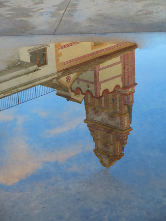 reflected: Belfry of Flores convent reflected in large rainwater puddle near Alora, Andalucia