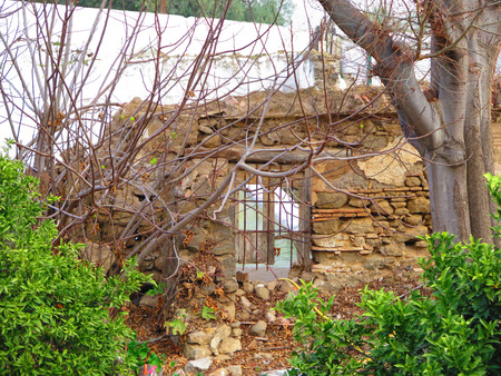 derelict: Barred Window in old derelict stone wall Stock Photo