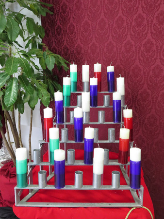 votive candle: Group of white votive candles in multicoloured plastic candle holders