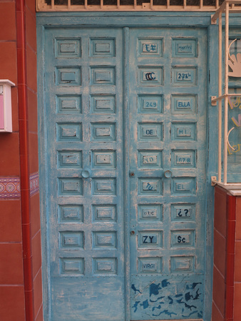 Fuengirola, Spain - March 3, 2016: Blue rusic painted wooden front door with writing and signs in panels in Fuengirola, Spain.