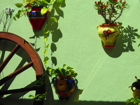 wall mounted: Waggon wheel and wall mounted flowerpots in Shade and sun in patio