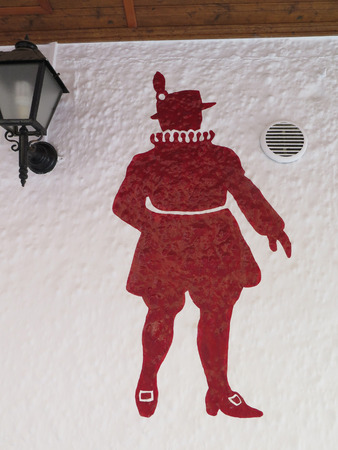 beefeater: FUENGIROLA, SPAIN - MARCH 3RD. Outline of red beefeater on white restaurant wall. Fuengirola, Spain. March 3rd 2016 Editorial