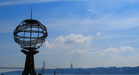 the tagus: The Iron Globe at The Monument to the Discoveries and the April 25th Bridge by the River Tagus in Lisbon, Portugal
