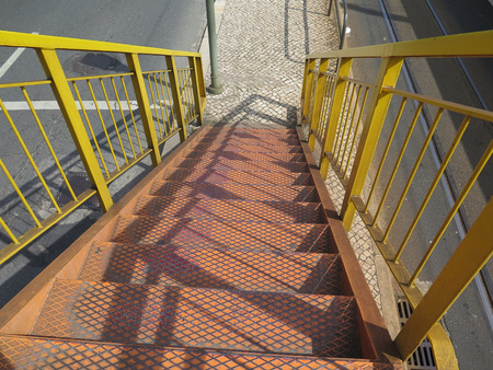 bannister: Yellow Steel stairs and railing leading down from road and rail overpass Stock Photo