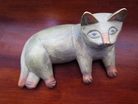 engaging: Carved wooden cat ornament, with an engaging facial expression.