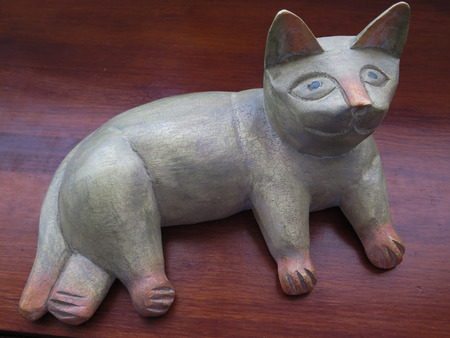 memorabilia: Carved wooden cat ornament, with an engaging facial expression.