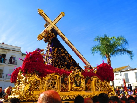 easter cross: Alora, Spain 25 March 2016: Jesus with large cross carried through village in  Easter procession