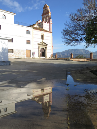 rainwater: Belfry of Flores convent reflected in large rainwater puddle near Alora, Andalusia
