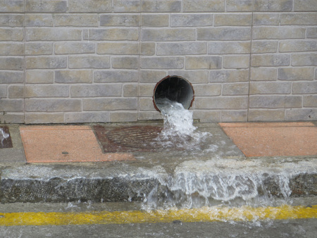 downpour: water gushing out of Rainwater drain pipe during torrential downpour Stock Photo