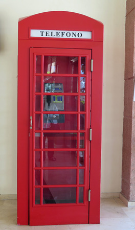 telephone: Red telephone box in spanish shopping centre