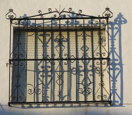 window grill: Wrought Iron Grill or bars on Window in Alora, Andalucia casting shadows on wall Stock Photo