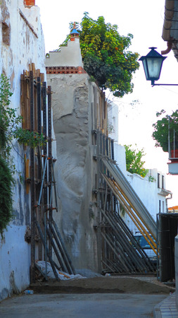 retaining: propping up retaining wall in narrow street in Alora, Andalusia