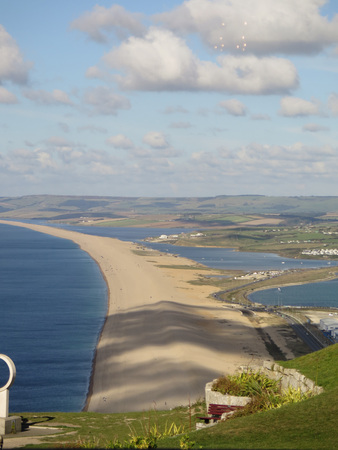View from Portland over the village of Chesil along Chesil Beach, with clouds creating shadows on beach