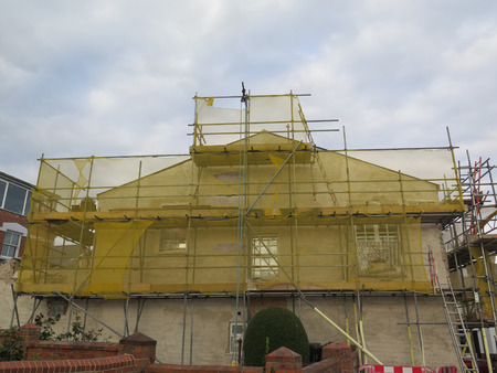 netting: Building renovation in English town, showing Scaffold and Yellow Netting