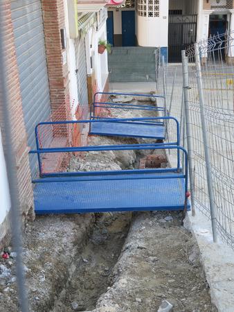 culvert: Blue steel gangways over drainage culvert in Spanish village street