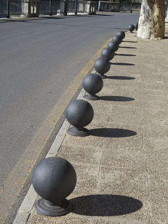 Metal Bollards casting Shadow on pavement in Andalusian village