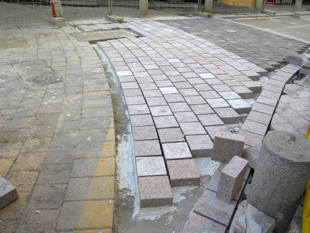 spacing: Square paving stones awaiting grouting in village street in Andalusia Stock Photo